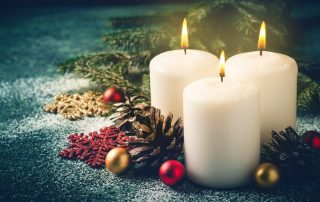 New Hair Clinic Three Christmas burning candles and decorations on dark turquoise background